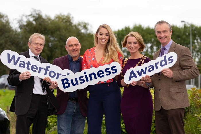 Group standing with signs for Waterford Business Awards