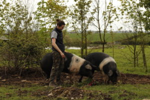 Chef Rose Greene on a farm with pigs