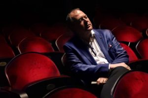 Dieter Kaegi Artistic Director of BVOF sits in a theatre with red chairs